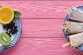 Draufsicht auf hausgemachte Eis am Stiel und frisches Obst auf Tellern auf rosa Holztisch