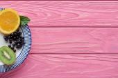 pohled shora čerstvé zralé plody a bobule na štítku na horní růžový dřevěný stůl