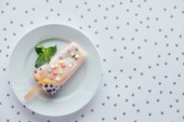 Fotografie top view of delicious fruity popsicle with mint leaves on plate and beautiful golden stars on grey
