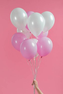 Cropped view of holding pink and white balloons in girl hand isolated on pink stock vector