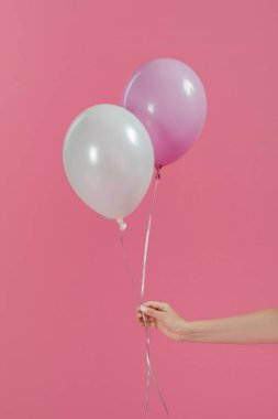 Cropped view of woman holding two balloons isolated on pink