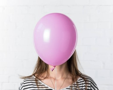 Pink balloon covering face of young woman on white brick wall background