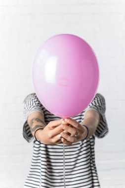 Girl holding pink balloon in front of her face on white brick wall background