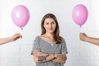 Smiling girl standing between hands holding pink balloons on white brick wall background