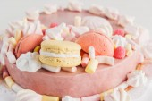 close up of pink cake with marshmallows and macarons