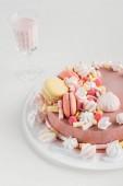 Fotografie růžový dort s marshmallows a macarons na desku a koktejl ve skle