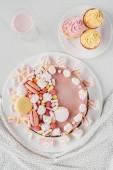flache Liege mit rosa Geburtstagstorte, Marshmallows, Cupcakes und Milchshakes auf Tisch mit Tischdecke