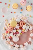 top view of sweet birthday cake with marshmallows on marble table with milkshake and cupcakes