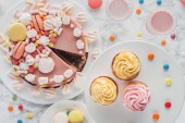 top view of birthday cake with marshmallows, cupcakes and milkshakes on table