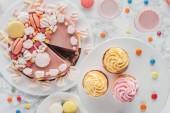 Fotografie pohled shora na narozeninový dort s marshmallows, košíčky a mléčné koktejly na stole