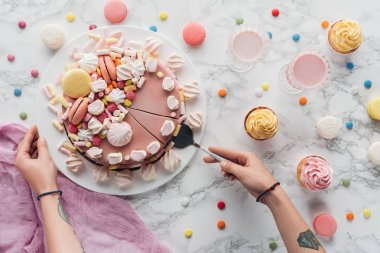 cropped view of woman taking piece of pink birthday cake with marshmallows and macarons