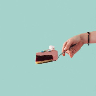 cropped view of tattooed hand with piece of cake on cake shovel isolated on blue