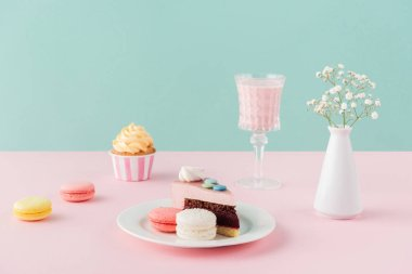 macarons, cupcake, piece of cake and milkshake on pastel background