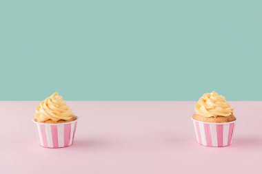 two cupcakes with buttercream on pastel background with copy space
