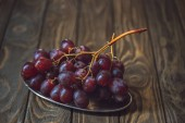 close-up shot of branch of fresh grapes on vintage metal plate on rustic wooden table