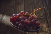 close-up shot of branch of ripe grapes on vintage metal plate on rustic wooden table