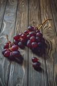 close-up shot of branches of red grapes on rustic wooden table
