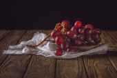 close-up shot of ripe grapes on cheesecloth and on rustic wooden table on black