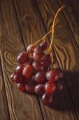 Detailní záběr zralé červené hrozny na rustikální dřevěný stůl