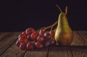 Fotografie close-up shot of ripe pear and grapes on rustic wooden table on black