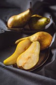 Fotografie close-up shot of sliced ripe pears on grey drapery