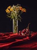 still life of grapes in metal bowl with flowers in vase on red drapery