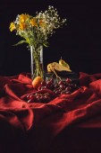 Fotografie still life with various fruits and flowers in vase on red drapery on black