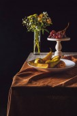 plate of pears and stand with grapes and vase of flowers on table on black