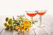 Fotografie close-up shot of glasses of wine with field flowers bouquet on wooden table on white