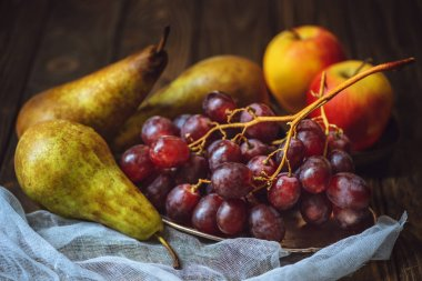 close-up shot of ripe grapes with pears and apples on cheesecloth