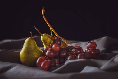 close-up shot of ripe pear and red grapes on grey drapery on black