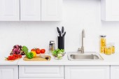 Fotografia pomodorini e peperoni su taglieri in cucina luce