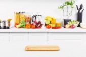Fotografie prázdné prkénko na stole s zralé zeleniny na pozadí v lehké kuchyni