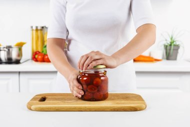 cropped image of woman opening glass jar with preserved tomatoes in light kitchen