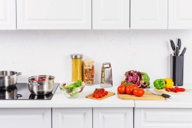 ripe vegetables on cutting boards, pans on electric stove in light kitchen