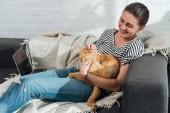 szép boldog fiatal nő ül a kanapé és a simogatás vörös macska