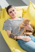 magas, szög, kilátás a lány gazdaság vörös macska és mosolyogva fényképezőgép sárga kanapén fekve