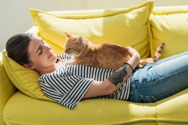 beautiful smiling young woman lying on yellow couch with cute red cat