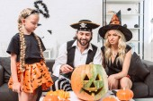 Photo family in halloween costumes on sofa at coffee table with pumpkins at home