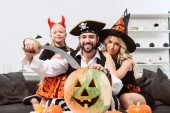 family in halloween costumes on sofa at coffee table with pumpkins at home
