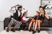 Fotografie otec a syn v kostýmech pirátů děsí matka a dcera na gauči doma