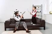 Fotografie otec a syn v pirátských kostýmech hraje doma, koncept svátek halloween