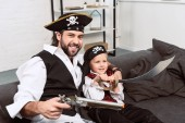 Fotografie portrét emocionální otce a syna v halloween kostýmy piráti sedí na gauči doma