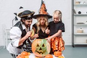 Fotografie portrait of parents and little daughter in halloween costumes looking into pumpkin together at home