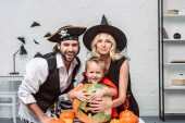 Fotografie portrait of happy parents and son in halloween costumes at table with pumpkins at home