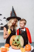 Fotografie portrait of mother and son in halloween costumes at table with pumpkins at home