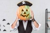Fotografia oscurava la vista delluomo in costume del pirata che copre il viso con la zucca, concetto di festa di halloween