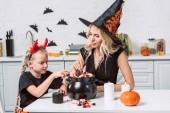 Fotografie matka a malá dcerka v halloween kostýmy u stolu se považuje v černý hrnec v kuchyni
