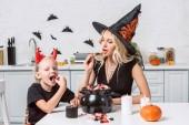 Fotografie matka a malá dcerka v kostýmech halloween jíst zachází černý hrnec v kuchyni