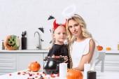 portrét matka a dcera v halloween kostýmy u stolu s sladkosti v černý hrnec v kuchyni doma